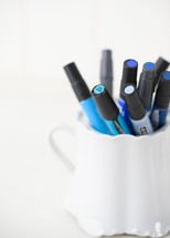 blue paint pens in a cup