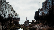 a man climbing rocks along a beach shore