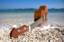 Guitar in the sand on the beach by the ocean.