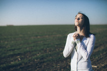 woman with her head lifted in prayer in a field