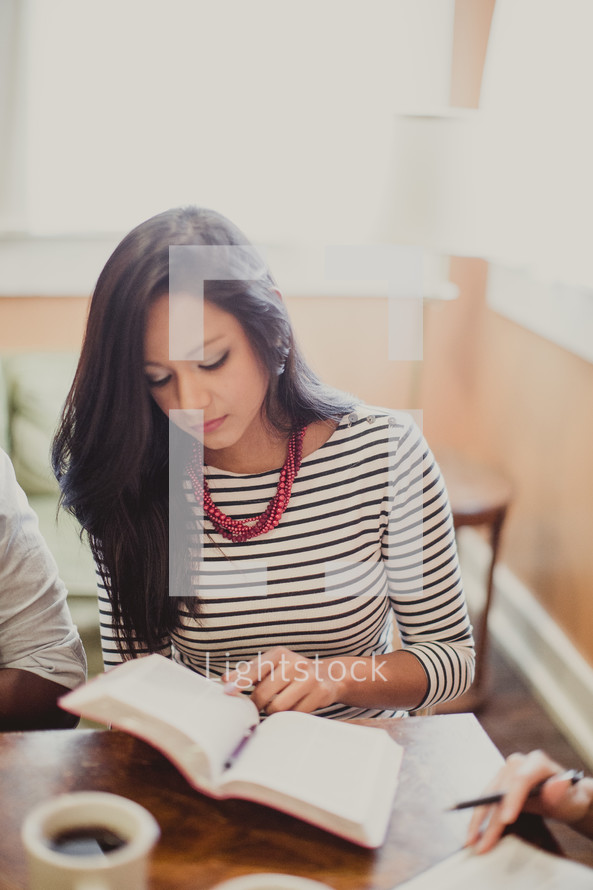 young woman reading a Bible at a table during a Bible study
