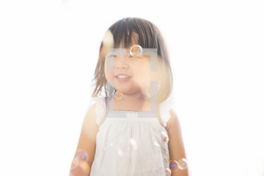 a little girl blowing bubbles
