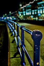 A blue railing along a street at night.