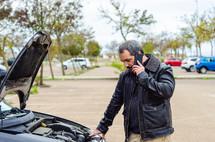 man standing next to a broken down vehicle