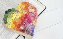 heart of buttons on the pages of a Bible