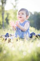 toddler girl sitting in grass clapping her hands