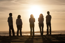 Sun shining on five young people standing on the beach.