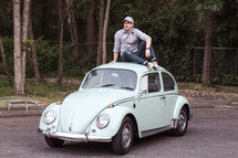 a man sitting on vintage Volkswagen Beetle