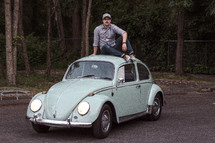 a man sitting on a vintage Volkswagen Beetle