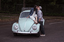 a couple kissing on a vintage Volkswagen Beetle