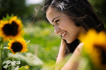 A smiling young woman standing among sunflowers.