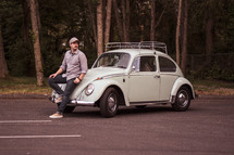 man leaning against a vintage Volkswagen Beetle