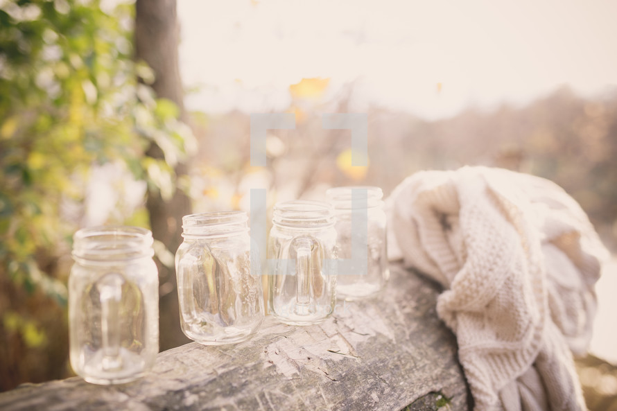 glass mason jars on a log