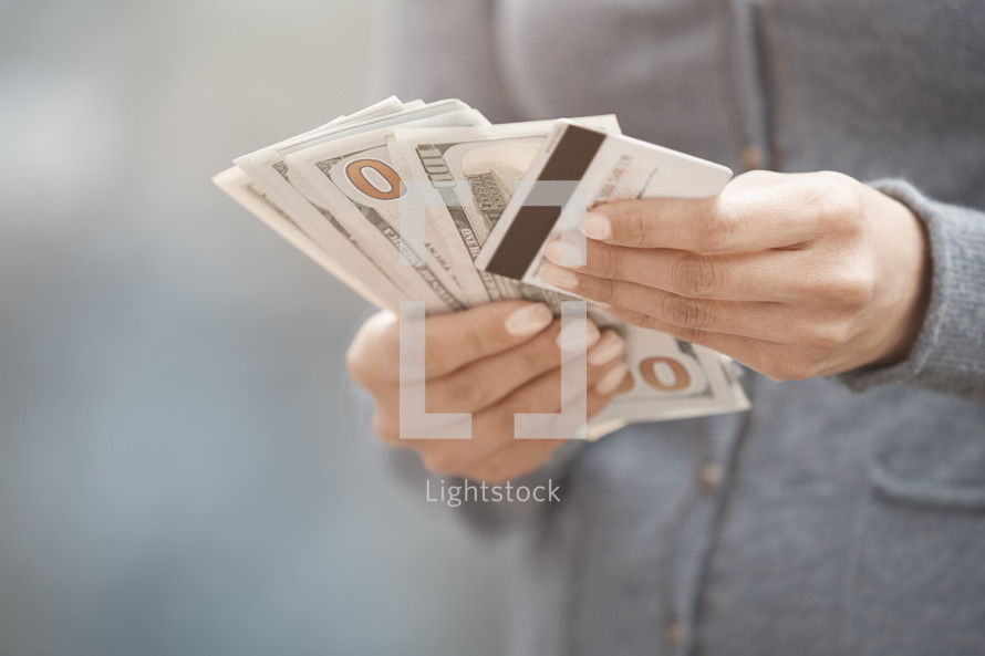 a woman holding cash and a credit card