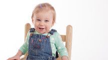 toddler girl in overhauls sitting in a chair