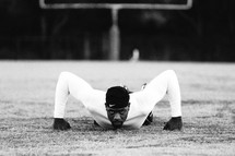 a man doing pushups on a football field