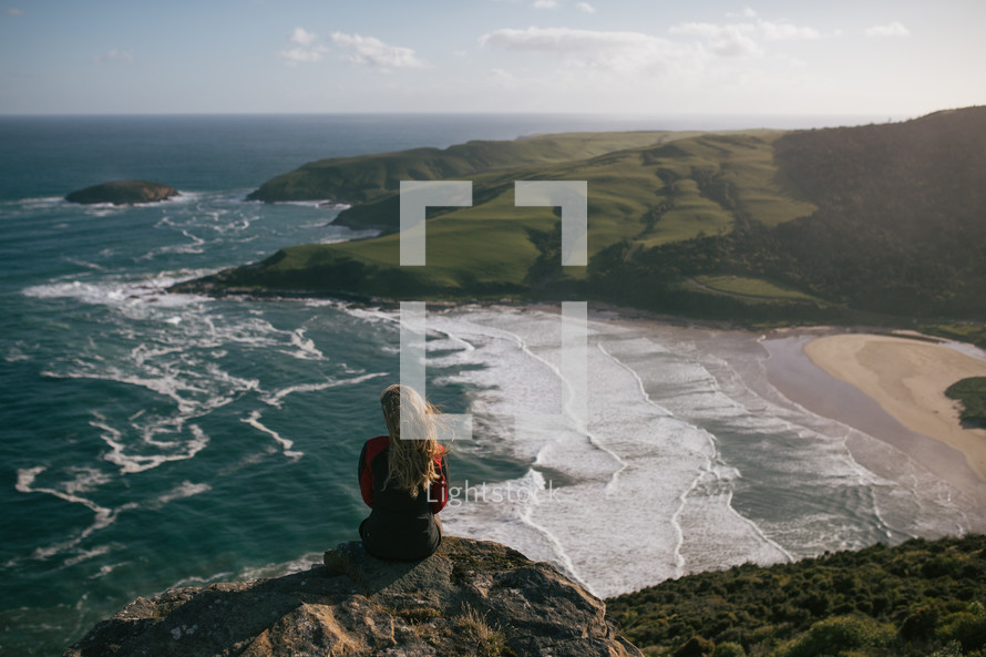 a woman sitting at the edge of a cliff in New Zealand