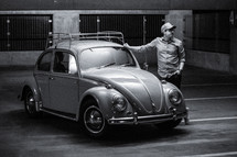a man leaning against a vintage Volkswagen Beetle