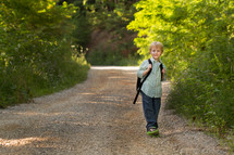 child with a backpack on a dirt road
