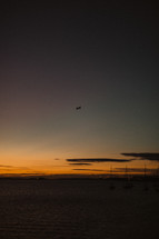 plane in the sky over water at dusk