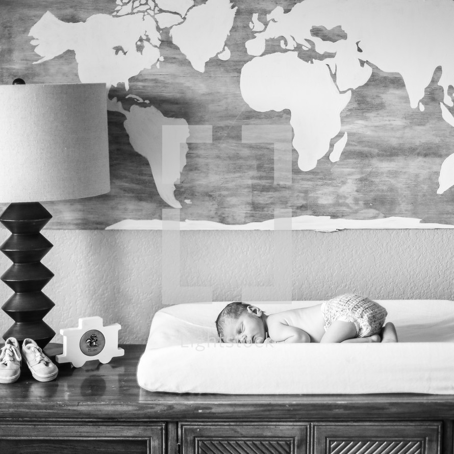 Newborn baby on a changing table under a world map