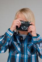 boy child holding a camera