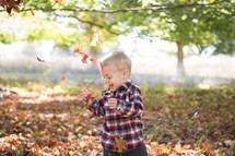 laughing child playing in leaves