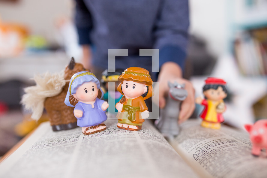 toy manger Biblical figures on the pages of a Bible
