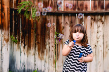 girl child blowing bubbles outdoors