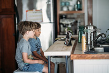 two boys sitting in a kitchen doing a video conference
