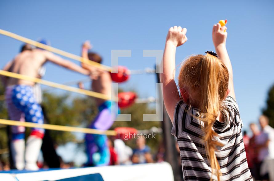 Child cheering at wrestling match
