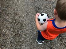 a boy carrying a soccer ball