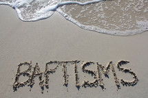 Word 'Baptisms' written in the sand