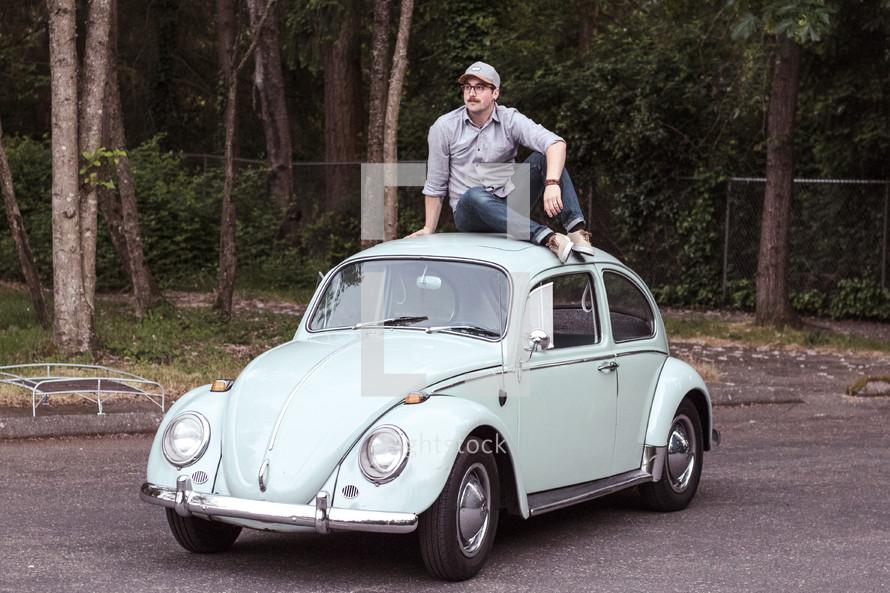 a man sitting on vintage Volkswagen Beetle