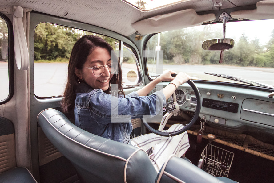 a woman driving a vintage Volkswagen Beetle