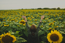 woman standing in a vast field of sunflowers
