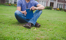 A man holds a Bible on a lawn outside an apartment complex