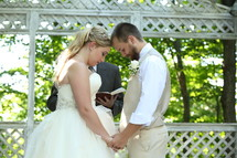 Young bride and groom praying while holding hands, preacher holding Bible in the background.
