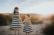 sisters walking holding hands on a beach