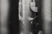 downtown alleyway with steam through fence