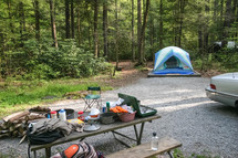 camping gear on a picnic table and tent at a campsite