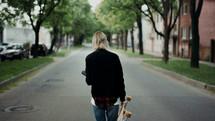 a young woman walking down a neighborhood street carrying a skateboard