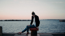 a woman sitting at a harbor at sunset