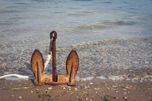 rusty anchor sitting upright on a shore