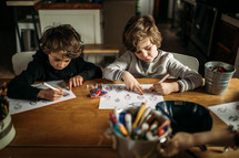 children coloring a coloring page at home