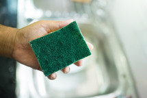 man holding a sponge over a sink
