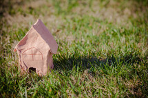 Handmade clay model of a home in the grass; day, outdoors, sun setting; As for me and my house, we will serve the Lord  (Joshua 24:15)