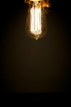 An old-fashioned lightbulb hanging from a ceiling
