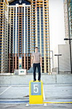 A man standing on a pedestal among tall buildings.