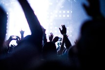audience at a concert with their hands raised and taking pictures with cell phones